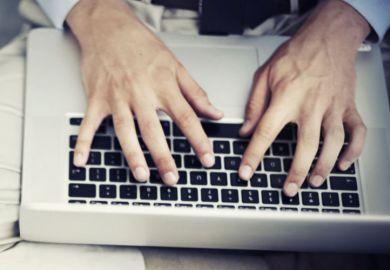 Man typing on Apple MacBook laptop keyboard