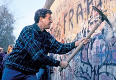 Man using pickaxe to break down Berlin Wall, 1989