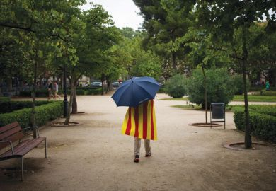 Man walks in rain wearing Catalan flag