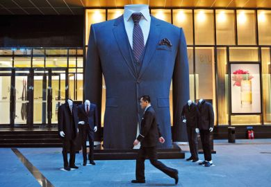 Man walks past huge suit, Shenyang, Liaoning province