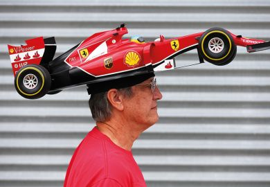 Man with F1 car on head