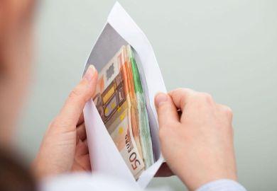 Man looking at euros in envelope