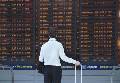 Man looking at airport departure board