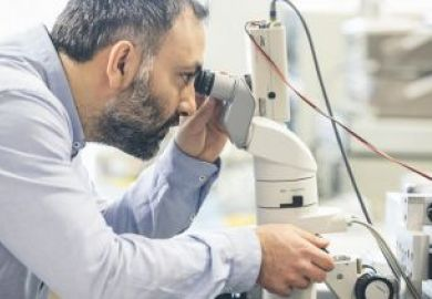 man_looking_through_microscope