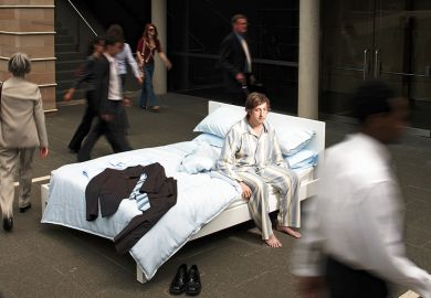 A man in pyjamas in a bed in the street