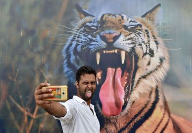 A man poses for a selfie with a tiger