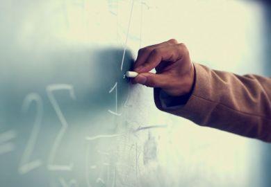 Man's hand drawing on blackboard