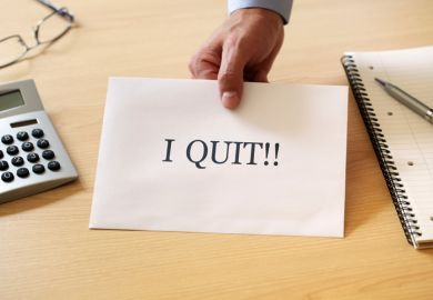 Man's hand holding 'I quit' resignation note