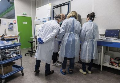 Laboratory technicians and biologists discuss testing procedures as they operate a ribonucleic acid extractor at the LBM LxBio medical biology laboratory in Rodez, France