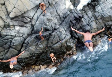 Men diving off cliff into sea