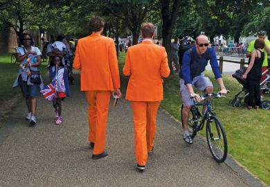 Men walk along wearing matching orange suits