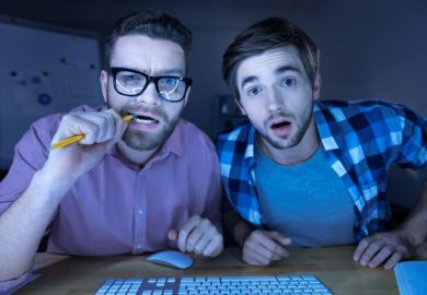 Men peering confused into computer screen
