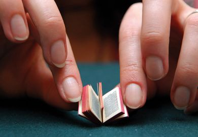 Person reading miniature book