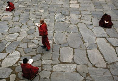 Monks studying books in the courtyard