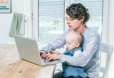Mother working on laptop in kitchen with baby
