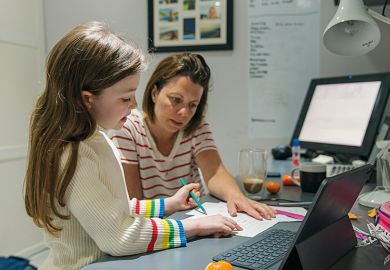 A mother helps child with homework