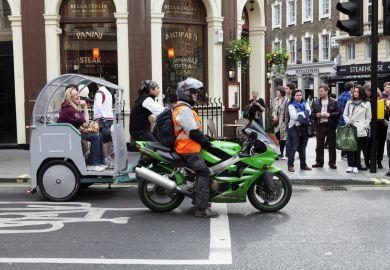 Motorbike and rickshaw at traffic lights