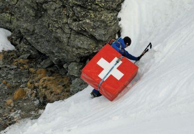 Mountain climber carrying safety mattress bearing Swiss flag