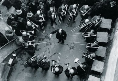 Musicians playing trombones around conductor