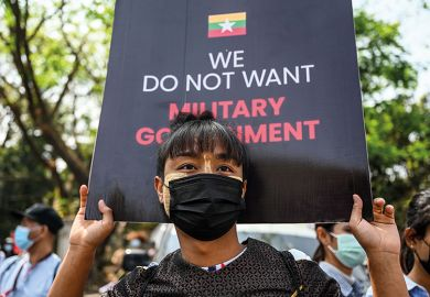 A man carries a sign during a protest next to Yangon University against the military coup in Yangon on February 25, 2021.
