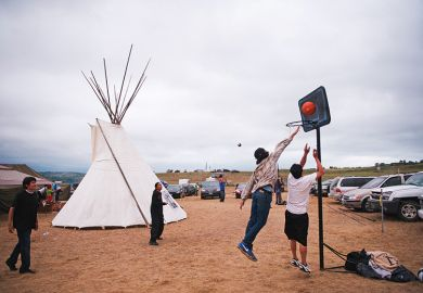 Native American protesters play basketball