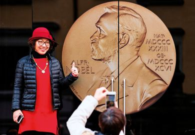 An Asian woman poses for a picture at the entrance of the Alfred Nobel Museum in Stockholm, Sweden, 2019.