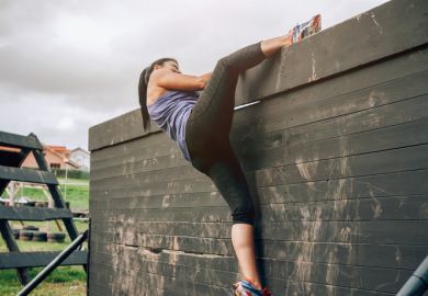 A woman climbing over a fence on an obstacle course