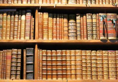 Old books arranged on library bookshelves