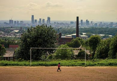 A general view of an old cotton mill in Oldham with the city of Manchester on the horizon, 2020