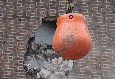 Orange wrecking ball demolishing building wall