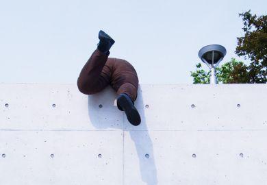 Overweight man scrambling over high wall