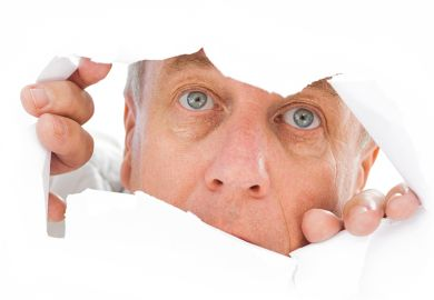 Man peeks through tear in paper