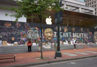 Passers-by stop and take a look at the boarded-up Apple Store in downtown Portland's Pioneer Place, which has become unofficial canvases for peaceful protest.