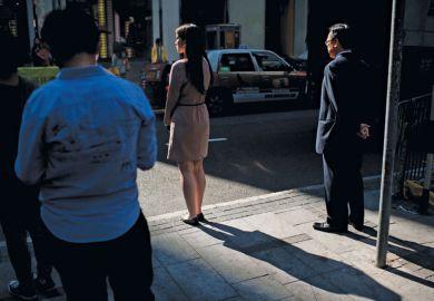 Pedestrians waiting to cross the road, Hong Kong