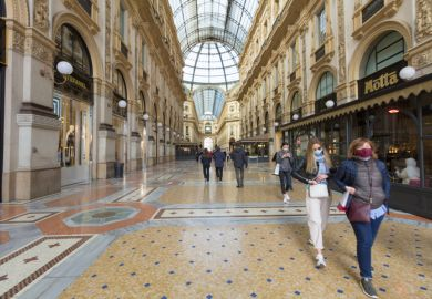 Pedestrians wearing protective face masks in Galleria Vittorio Emanuele II in Milan
