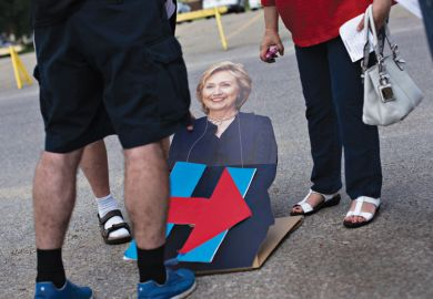 People looking at cardboard cutout of Hillary Clinton lying on road