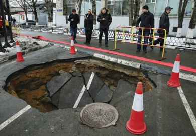 People looking at sinkhole in road