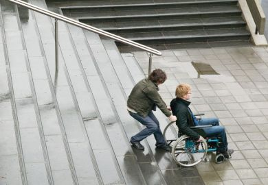 Person helping man in wheelchair up stairs