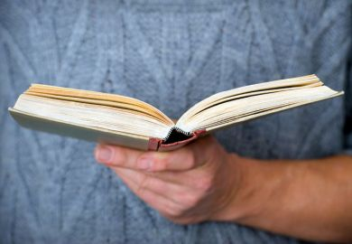 Person holding open book in hand