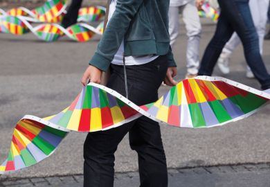 Person in street holding paper replica of DNA strand