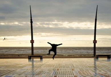Person jumping for joy on seafront promenade