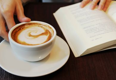 Person reading and drinking coffee