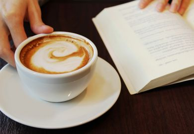 Person reading book and drinking coffee
