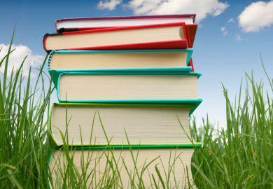 Pile of books on grass, summertime