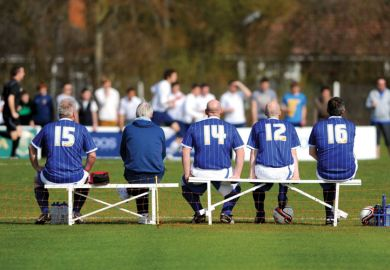 Players sitting on bench at football game