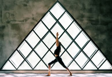 woman doing yoga by large triangular window