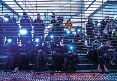 Pro-democracy demonstrators raise flashlights outside West Kowloon Magistrates' Courts during a hearing for 47 opposition activists charged with violating the city's national security law in Hong Kong, China, on March 4, 2021.