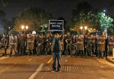 A man holds a placard saying 'Black Lives Matter' before a line of policemen