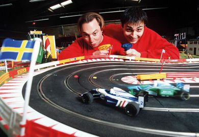 Two men beside a toy race track
