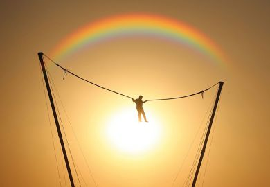 person bouncing in front of rainbow